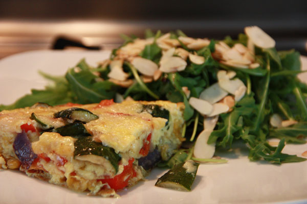 Fritatta on a plate with arugula and toasted almonds
