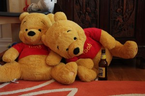 Two Pooh Bears, with bottle of beer toppled
