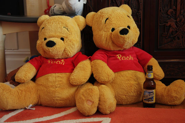 Two Pooh Bears sitting next to each other with a beer