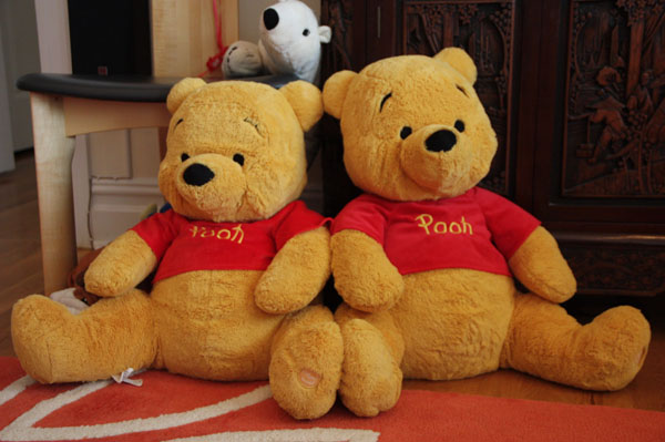 Two Pooh Bears sitting next to each other