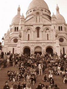 People sitting on the steps infront of Sacre Coeur