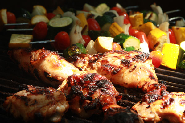 Jerk chicken and vegetable kabobs on a BBQ