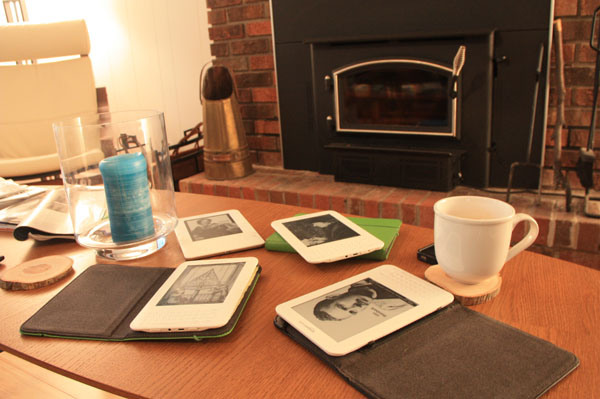 Four Kindles on a coffee table