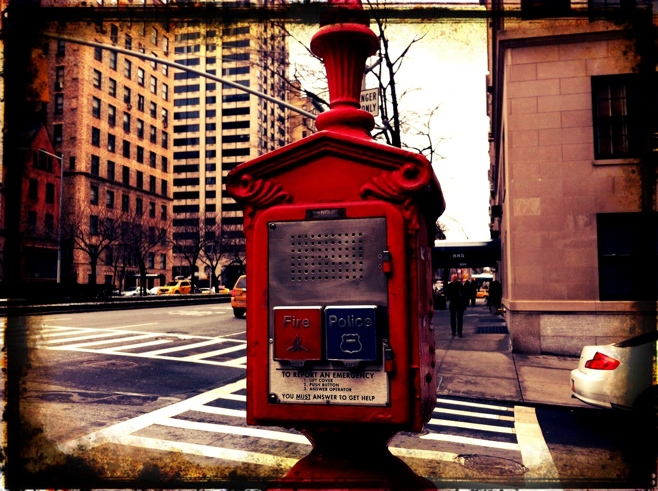 Red emergency call box on a corner street