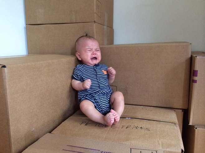 Crying baby sitting on boxes