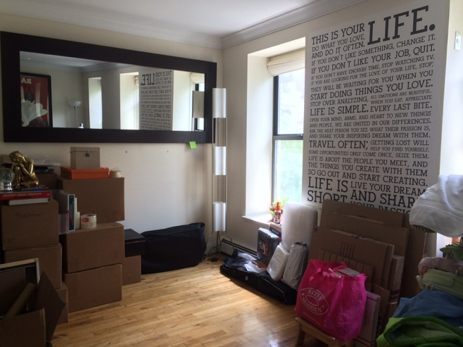 Apartment with boxes and items piled along the walls