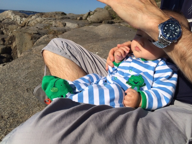 Baby sitting with dad on rocks overlooking the sea