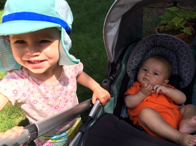 Baby in a stroller with little girl in a sun hat
