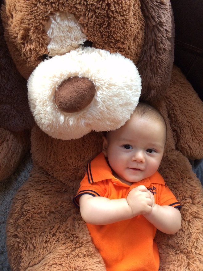 Baby with big stuffed toy dog