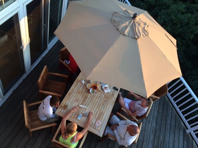 People sitting under a sun umbrella on a deck