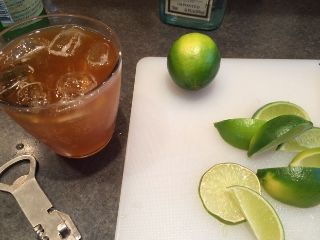 Drink and limes on cutting board