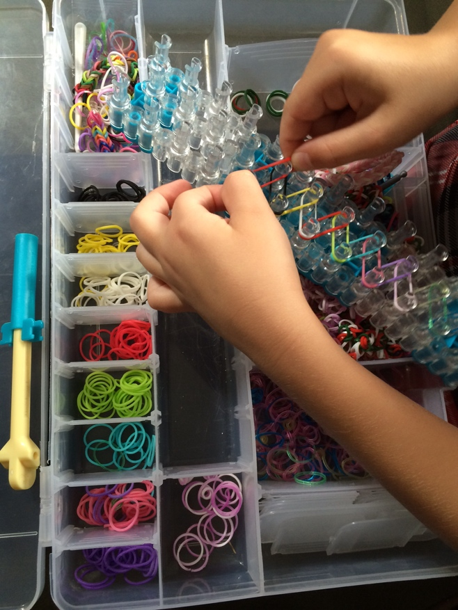 Girl making a rainbow loom bracelet