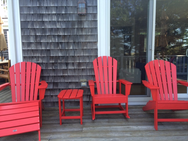Red adirondack chairs on a deck
