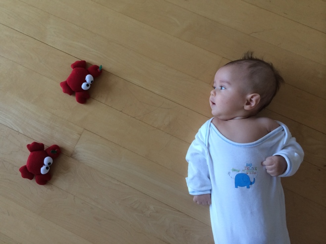 Baby on floor with two toy red crabs