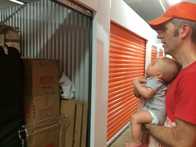 Man and baby looking at full storage unit