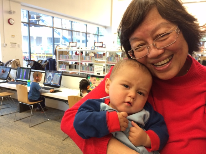 Baby with frowning face carried by grandma