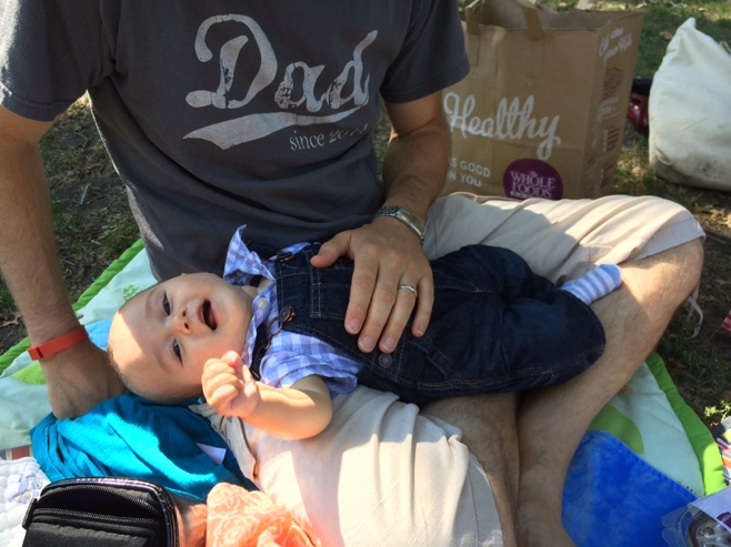 Man wearing dad T-shirt and baby on his lap