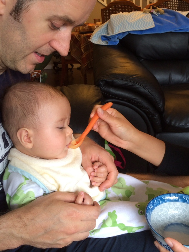 Dad holding baby eating first food