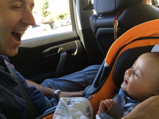 Baby in car seat smiling at dad