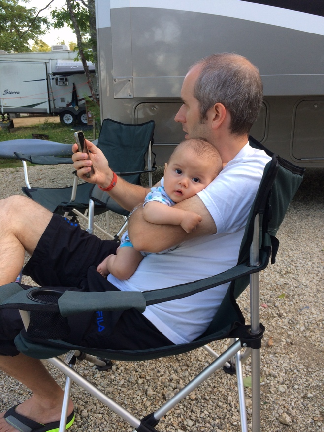 Baby in dad's arms sitting on camping chair