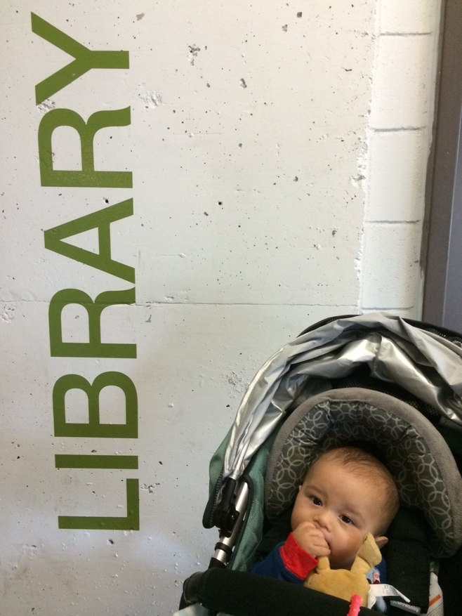 Baby in stroller in front of library sign