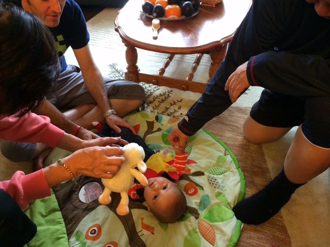 Baby on play mat with dad, grandpa and grandma