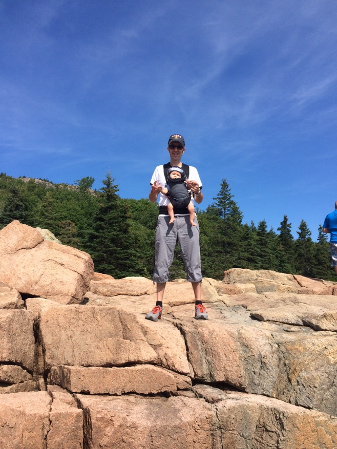 Baby and dad standing on rocks