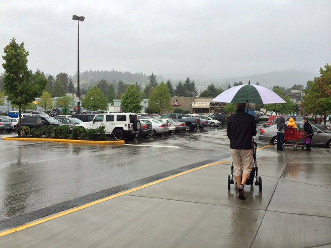 Man pushing stroller in the rain holding umbrella