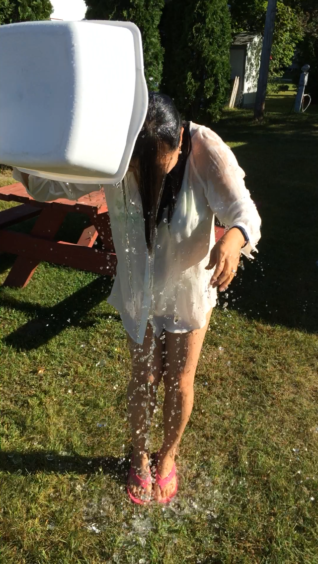 Woman tipping a bucket of ice water over herself
