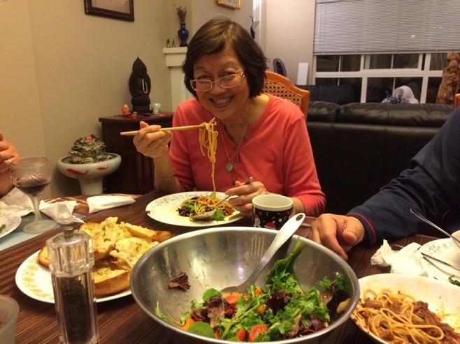 Mum eating spaghetti bolognaise with chopsticks
