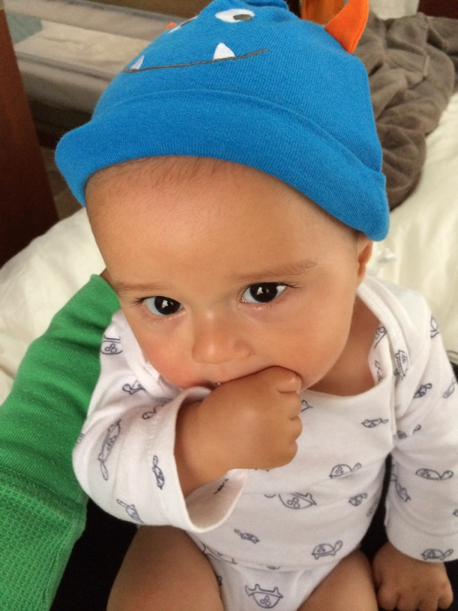 Baby with thumb in mouth and cute hat