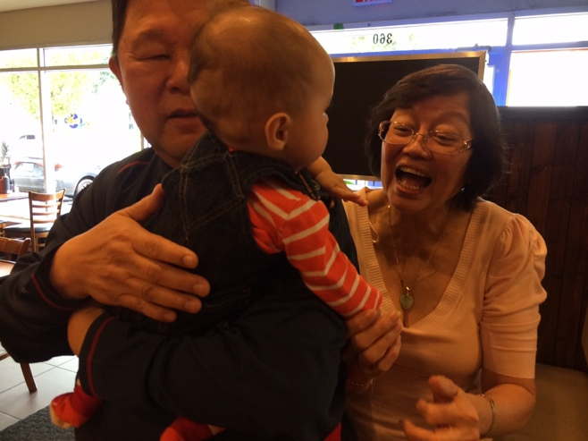 Baby held by grandpa with grandma talking to him