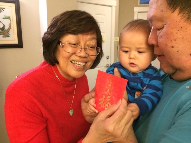 Grandparents giving baby a red packet