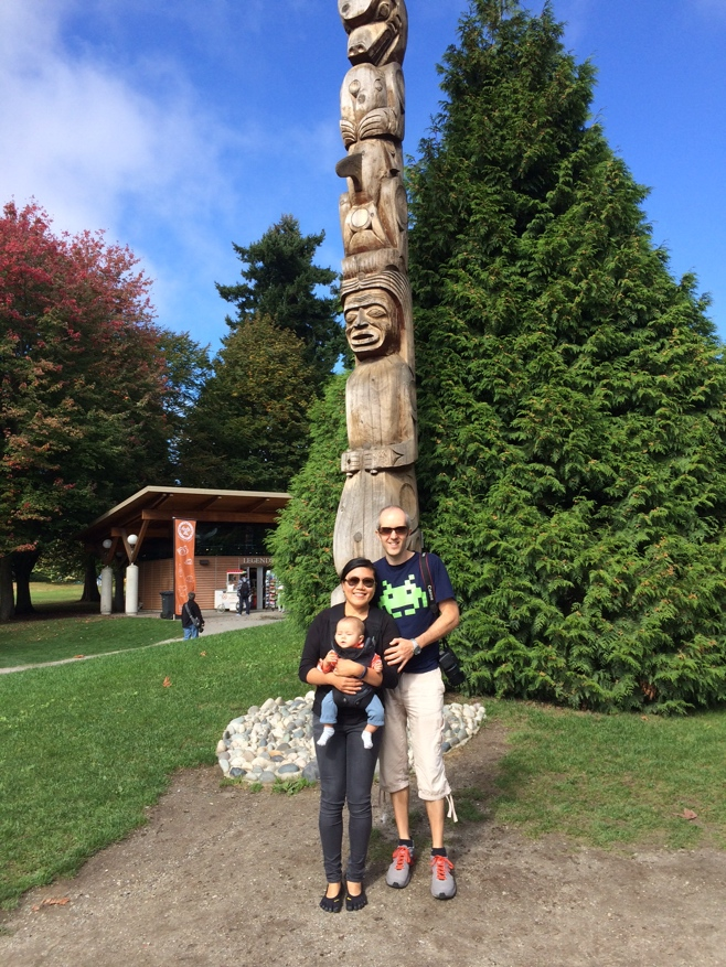Family posing in front of totem pole