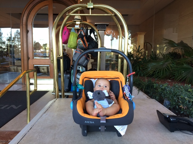 Baby in car seat in front of hotel with bags in background
