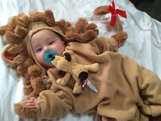 Baby in lion cub costume with pacifier