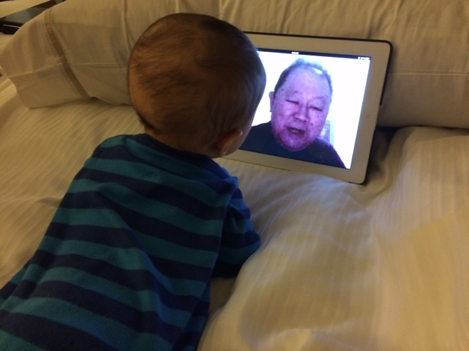 Baby lying on bed talking to grandpa