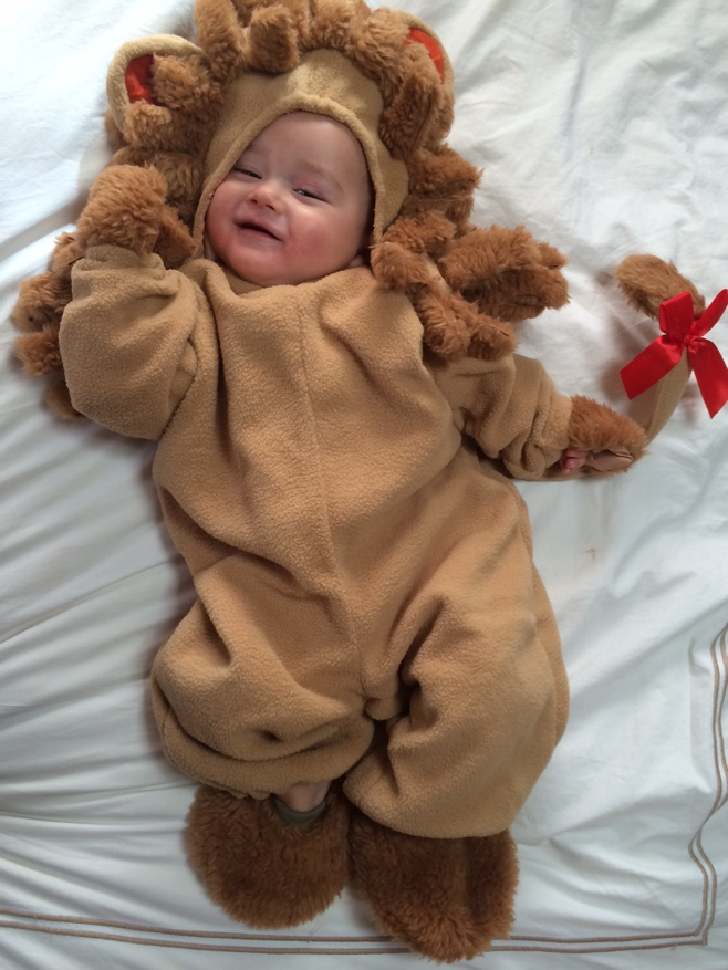 Baby lying on bed with lion cub outfit