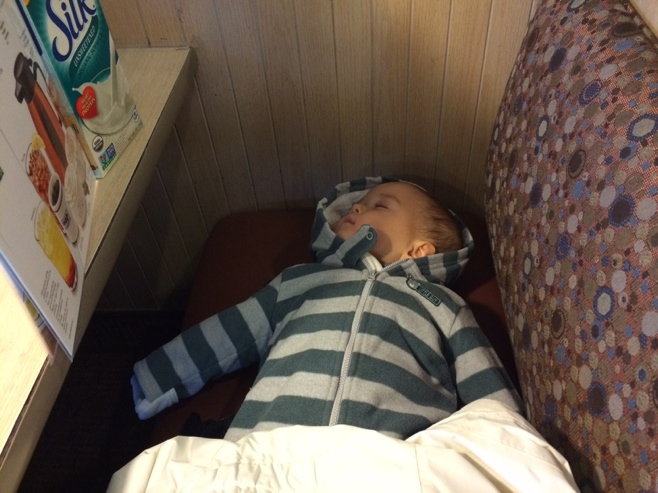 Baby napping on diner bench