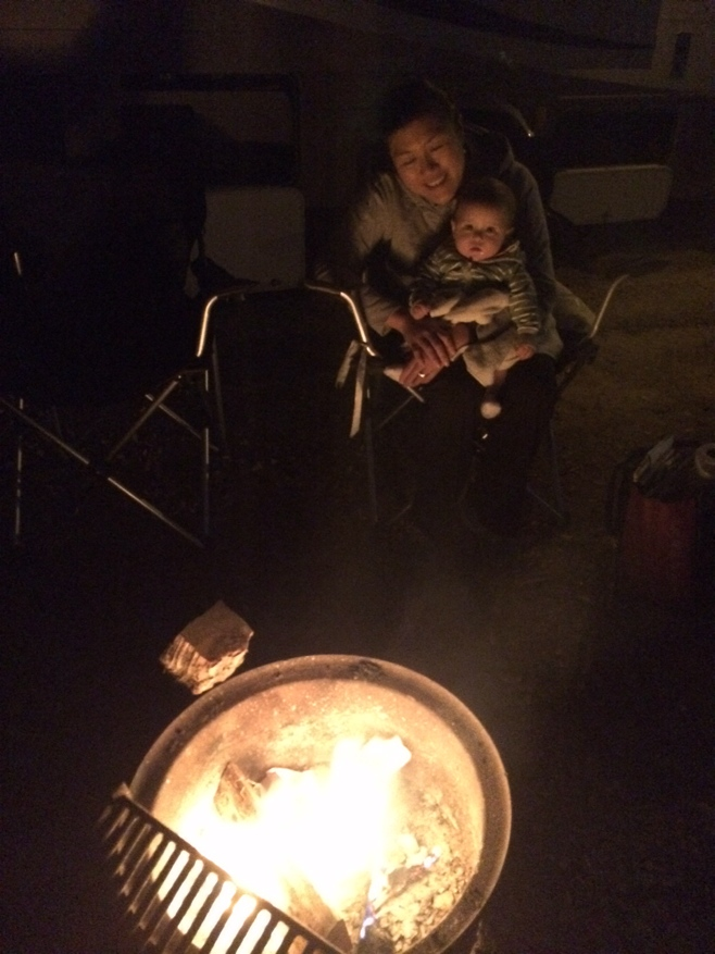 Baby and mum sitting by the campfire
