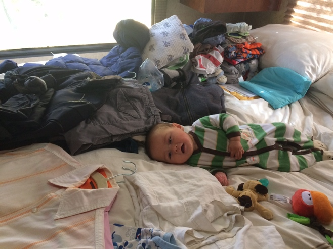Baby on bed with clothes all around him