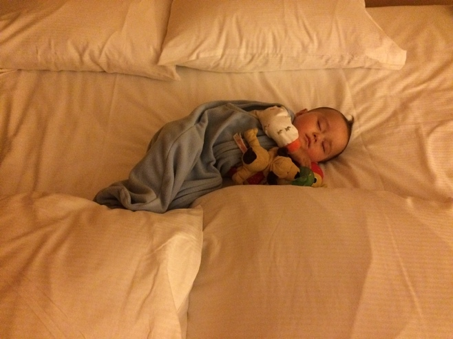 Baby sleeping on bed surrounded with pillows