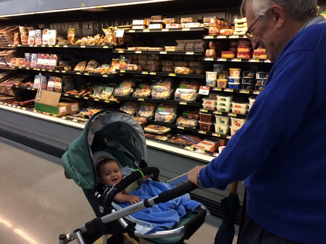 Grandpa pushing baby in stroller in Walmart