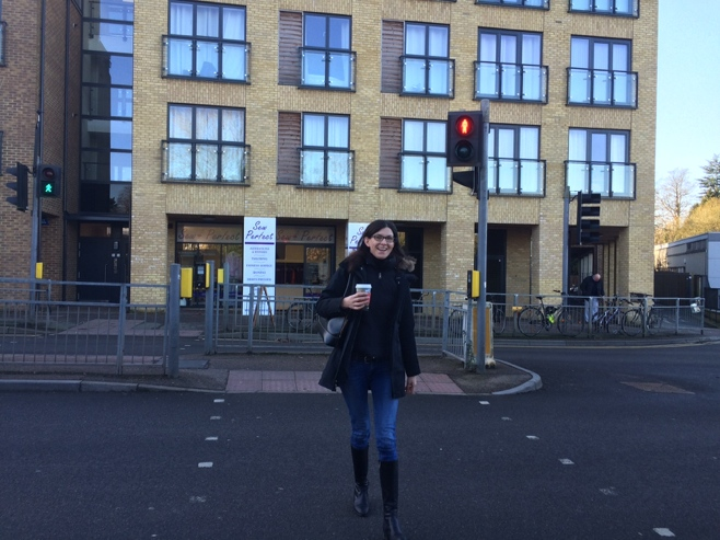 Woman crossing street with coffee
