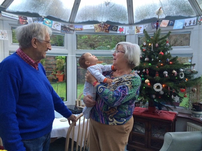 Grandparents and baby looking at Christmas decorations