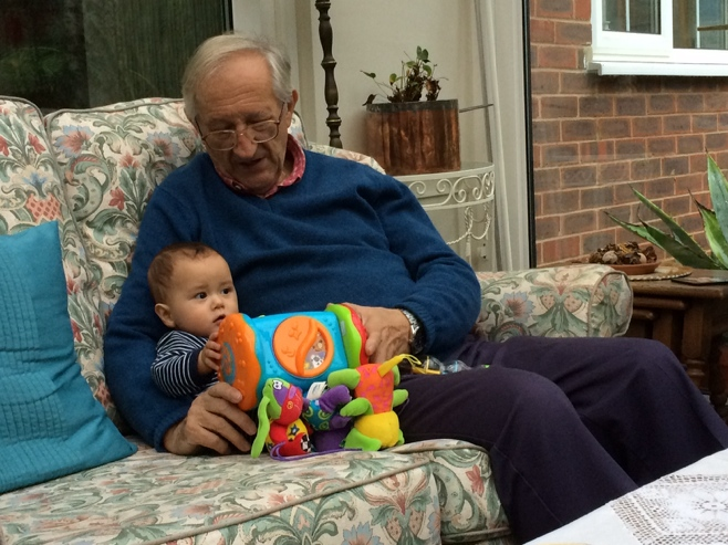 Baby and grandad on couch with toy