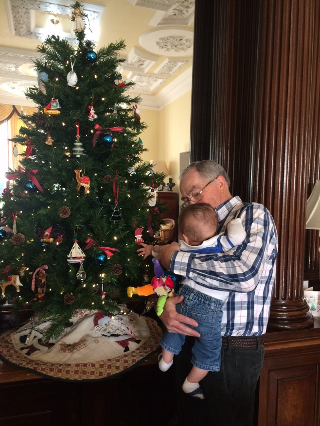 Baby and man looking at a Christmas tree