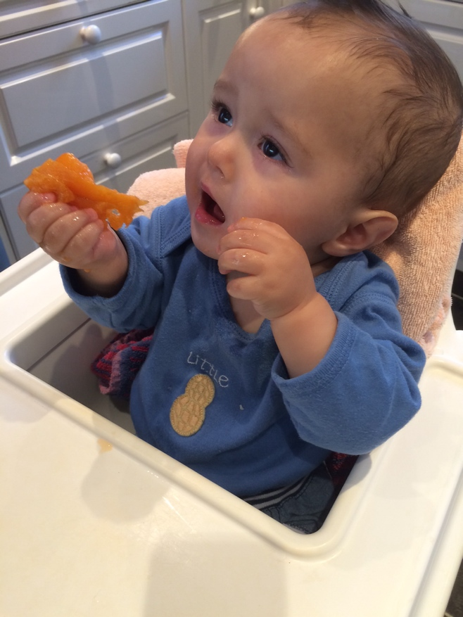 Baby eating apricot in high chair