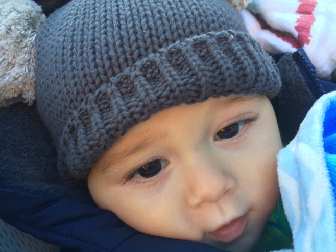 Baby in hat rugged up