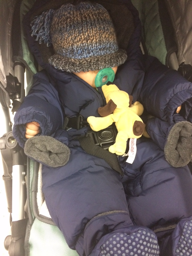 Baby in snow suit with wooly hat covering eyes